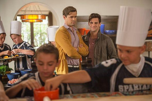 """Bryan and David watch as the junior football team enjoys Bryan's """"plan your own pizza party."""""""