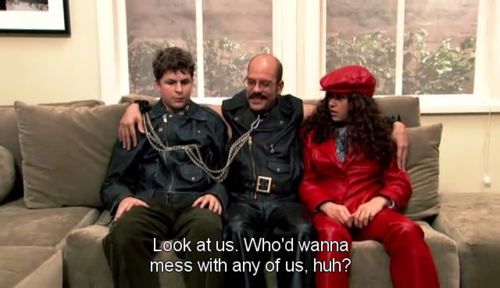 Screen capture from Arrested Development showing Tobias and George Michael wearing typical gay-macho attire. Would this be considered a subversion or a perversion to heterosexual man of power? To what extent can the gay-macho be considered a true parody of heteronormativity?